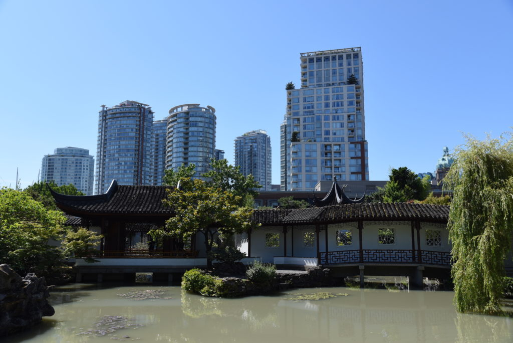 Chinese garden with modern buildings in the background