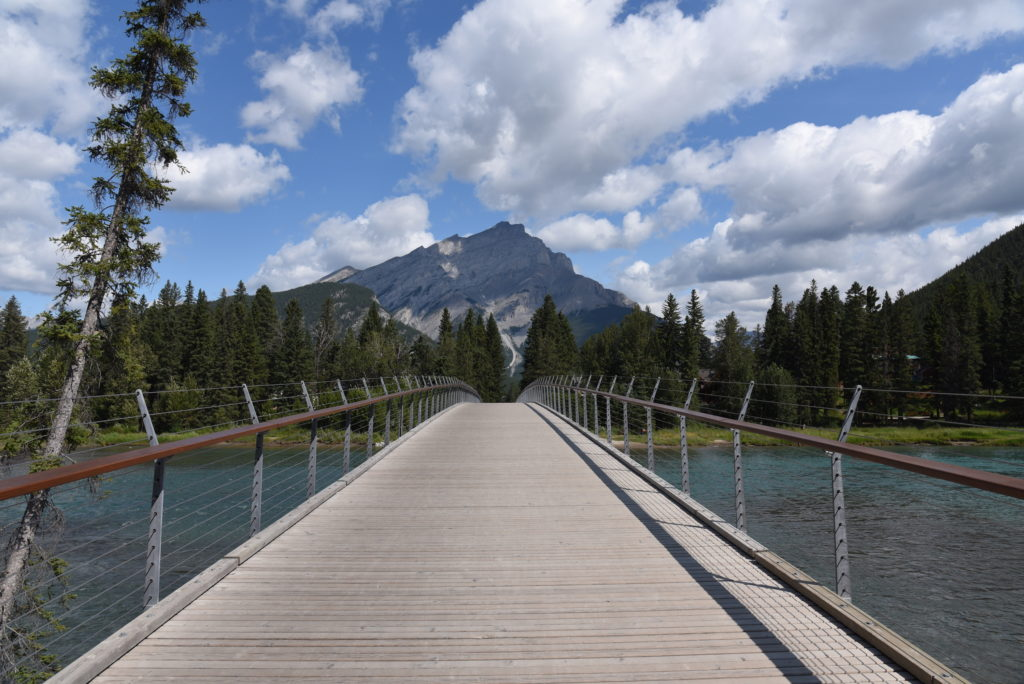 footbridge over Bow River, trees and mountain in the background