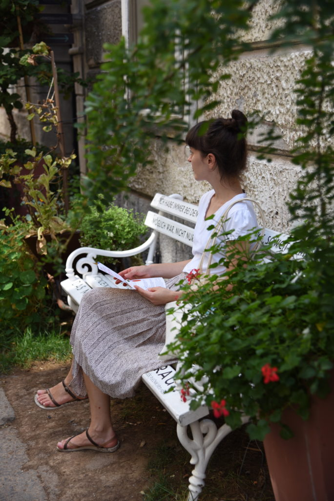 woman sitting on a bench surrounded by plants