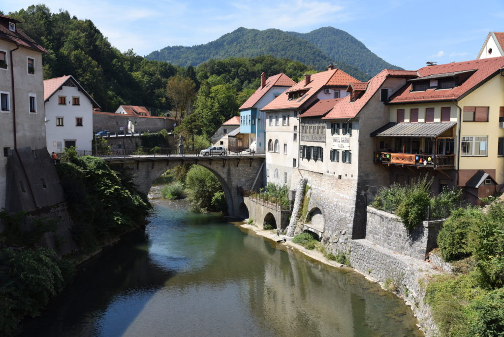 river with bridge over it and buildings by its side in Škofja Loka