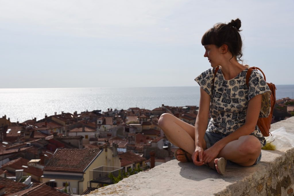 woman sitting on wall, overlooking old town of Piran and the sea
