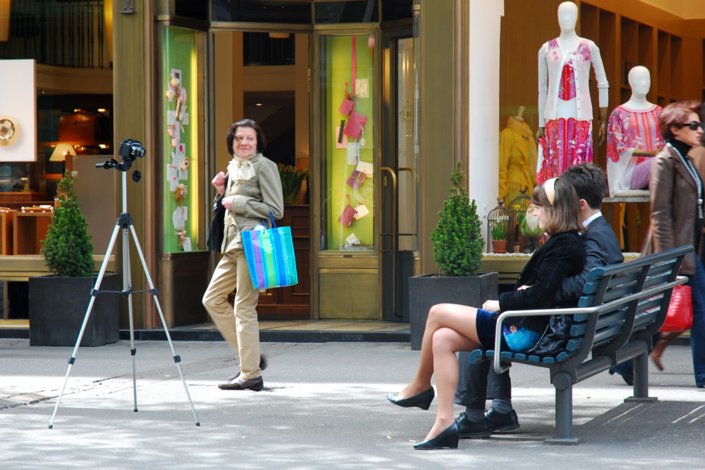 two people sitting on a bench taking a photo with timer and a tripod