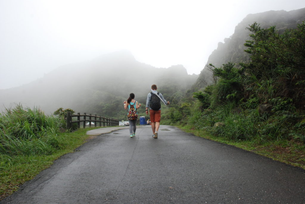 two people walking on a road, in nature and fogg