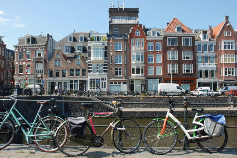 bicycles next to a canal, buildings in the background