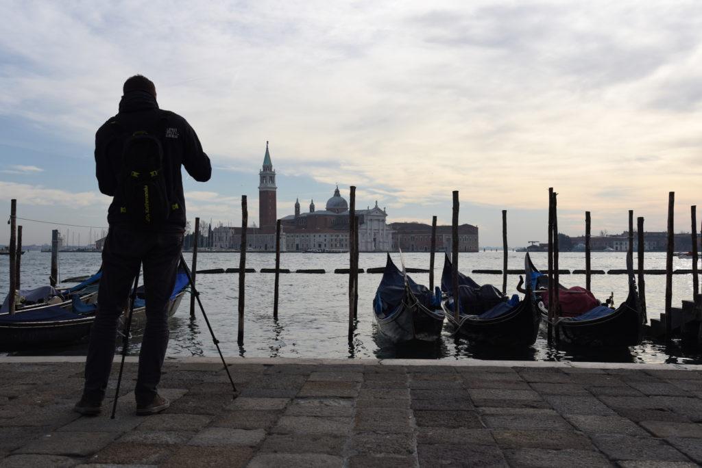 Photographer taking photos of canal, gondolas, church