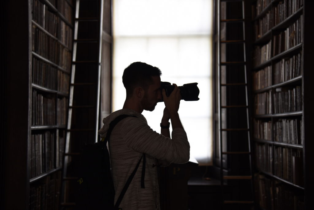 man taking photos in library