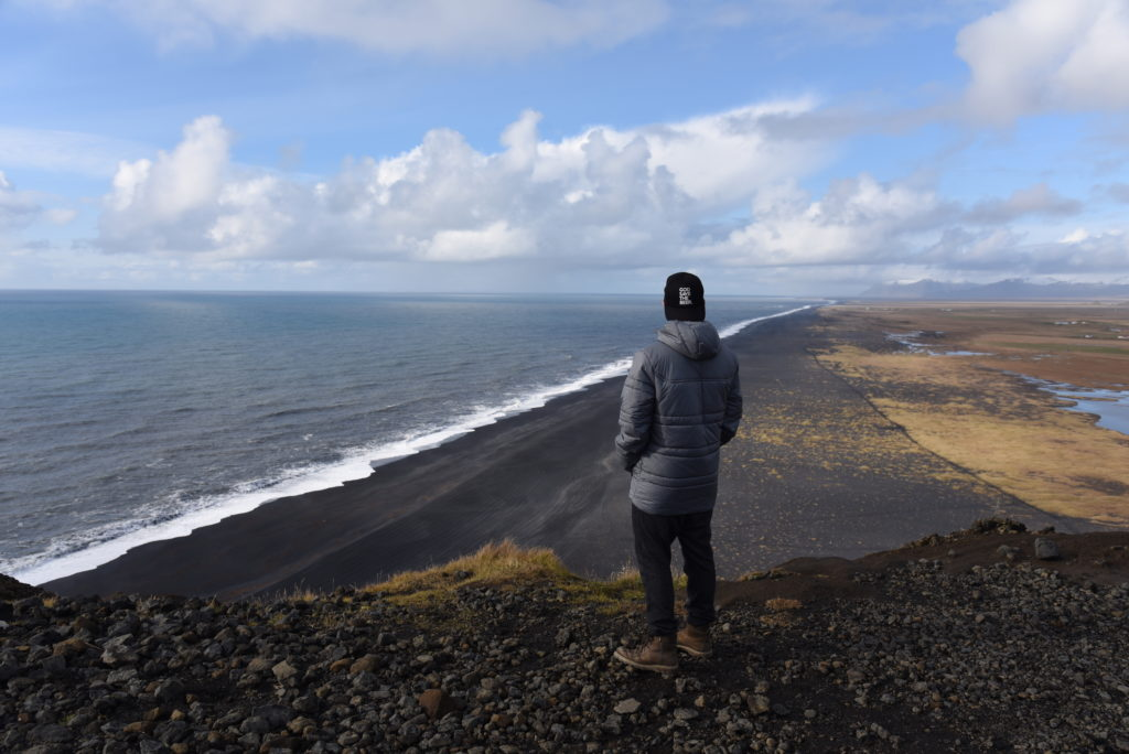 man overlooking black sand beach and sea