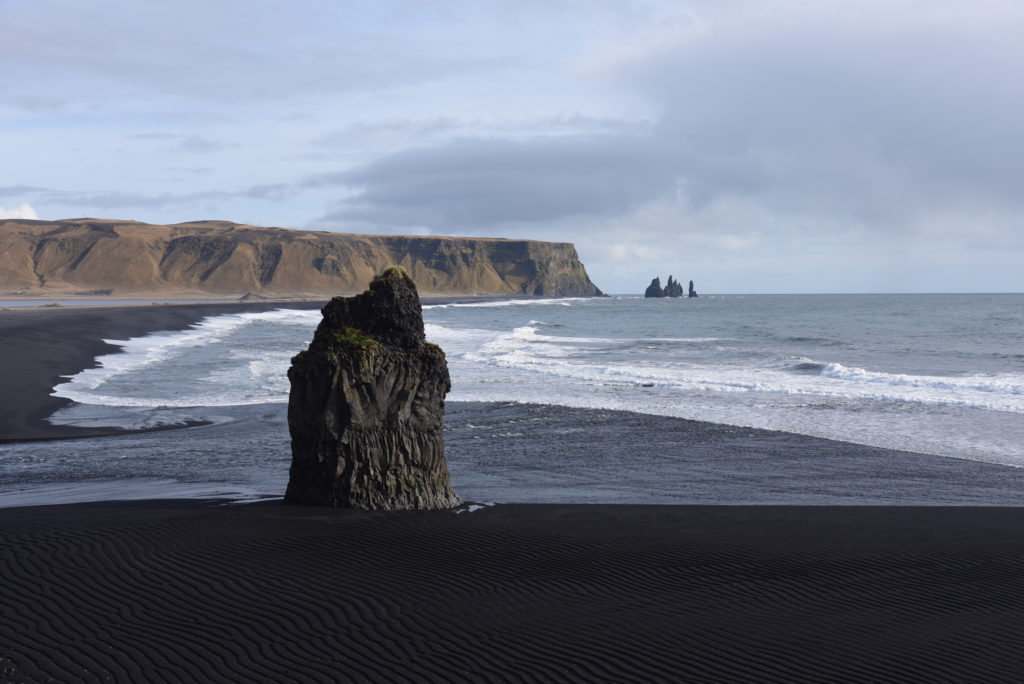 black sand beach with rock formation